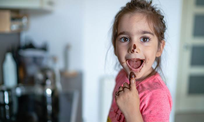 Girl eating chocolate with her finger